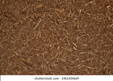 Brown background of chipped mulch pieces in a garden seen in full-frame from directly above. Used as fertilizer and retaining water for garden plants.