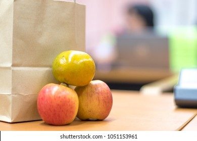 Brown bag lunch meeting concept. Paper bag contains food, snack, fruit and water  for officer in office in conference with hand on colleague working on table.