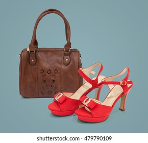 Brown bag and red sandals on plain background