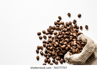 Brown beans with burlap bag on the white table. Harvest of coffee in different countries. Choice of the best sort and quality coffee. Empty place for a text.
