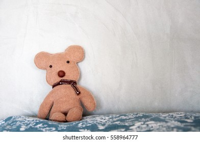 Brown bear doll sitting on pillow leaning on the concrete wall