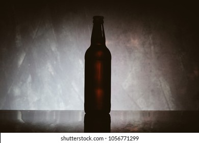 A brown beer bottle or cider, on a light blue background. A cold bottle of dark beer, on a black background with blue light. A brown beer bottle on a gray background. vintage photo processing