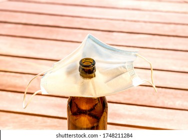 Brown beer bottle and face mask with hole for drinking, top view