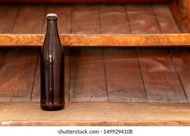 A brown beer bottle on a wooden staircase. Alcohol on the construction site