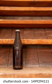 A brown beer bottle on a wooden staircase. Alcohol on the construction site. Portrait