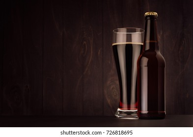 Brown beer longneck bottle and glass weizen with porter on dark wood board, copy space, mock up. Template for advertising, design, branding identity.