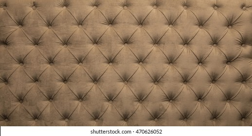 Brown beige velvet capitone textile background, retro style checkered soft tufted fabric furniture diamond pattern decoration with buttons, close up