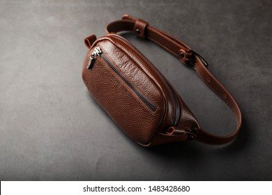 A brown belt bag made of textured brown leather on a black stone background. Elegant fanny pack brown bag with a zipper