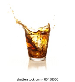 brown beverage splashing into a glass isolated