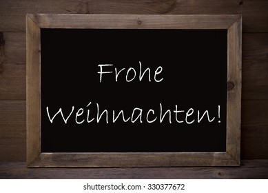 Brown Blackboard With German Text Frohe Weihnachten Means Merry Christmas As Greeting Card. Wooden Background. Vintage Rustic Style.
