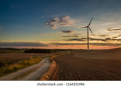 Brown and blue sunset at countryside with wind turbine