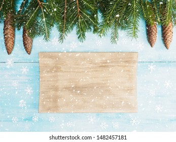 Brown and blue wooden Christmas background with snow, cones and fir branches. Christmas and New Year concept