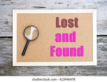brown board on a wooden table. magnifying glass on left side of the board. message on board says lost and found