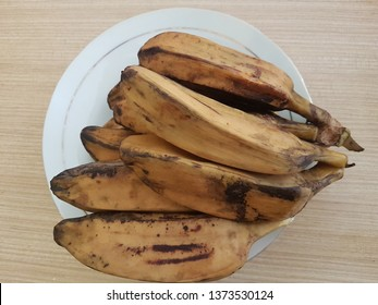 Brown boiled banana (pisang rebus coklat) on the white plate on the wooden table. Top view close up details.