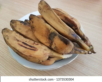 Brown boiled banana (pisang rebus coklat) on the white plate on the wooden table. Side view close up details.