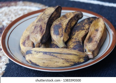 Brown boiled banana (pisang rebus coklat) on the white plate on on the patterned carpet. Side view close up details.
