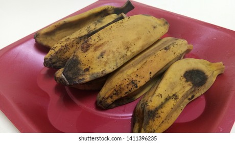 Brown boiled banana (pisang rebus coklat) on the white plate. Side view close up details.