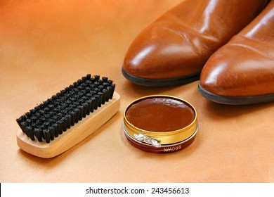 Brown boots with shoe polish and brush shoe care background.