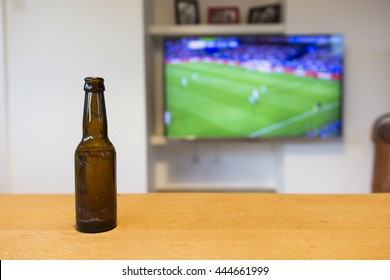 A brown bottle of beer standing on a wooden table. A soccer match on tv is visible in the background, which is blurred out.