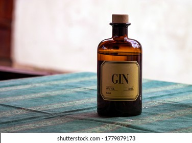 Brown bottle of medicine or alcohol with a label that say Gin on table