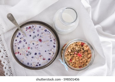 Brown bowl with muesli in milk, a bottle of milk and granola in jar. View from above.