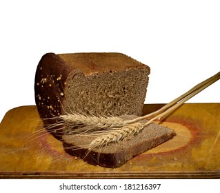Brown bread with slices and spikelets of wheat  on a wooden board