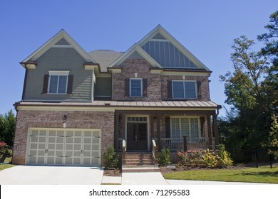 A brown brick two story house under a clear blue sky
