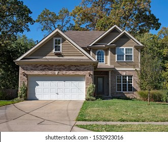 Brown Brick & Vinyl Sided Home with Arched Window in Fall
