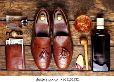 Brown brogues, and men's accessroies cufflinks,golden watch, tobacco pipe , ginger,bottle and glas of whiskey, leather  wallet with money .Set of gentlemen.Top view