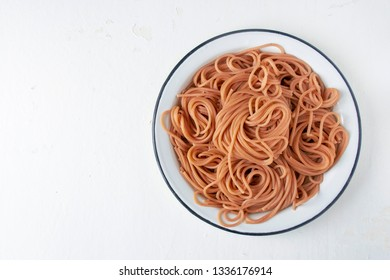 Brown buckwheat pasta on a light wooden background, the concept of a healthy diet. Close-up and copy space