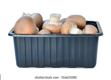 Brown cap cremini mushrooms in plastic box isolated on white background.