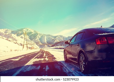 The brown car in the mountains the road.Extreme Winter Road Conditions. Snow-capped mountains