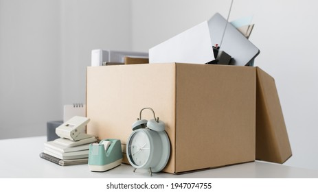 Brown cardboard box inside contains office equipment and resignation envelopes, Relocating or changing jobs or getting promoted, Resignation letter.