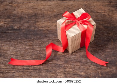 Brown cardboard box with red bow and ribbon isolated on a white background