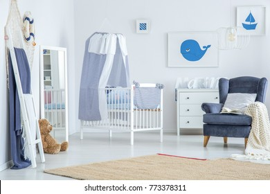 Brown carpet on the floor in baby's room with striped veil above crib near mirror, plush toy and armchair