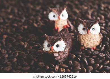 brown ceramic owls on roasted coffee beans background, wakw up coffee concept.