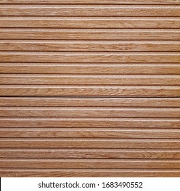 Brown ceramic tile with geometric pattern for wall decor. Concrete stone background. Texture with horizontal panels imitating wooden surface for interior design project.