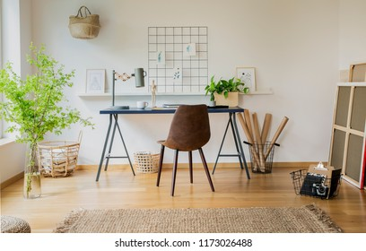 Brown chair at desk with plants and lamp in white workspace interior with carpet. Real photo