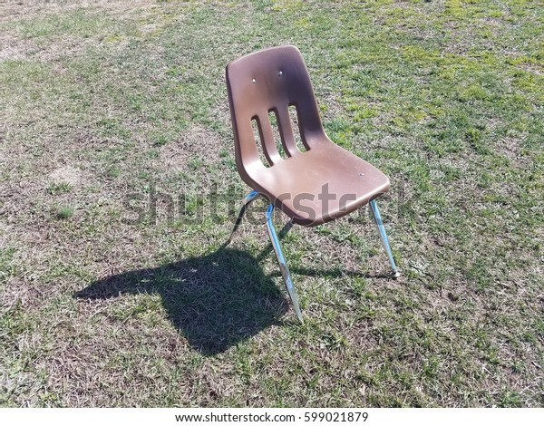 brown chair with shadow in the green grass