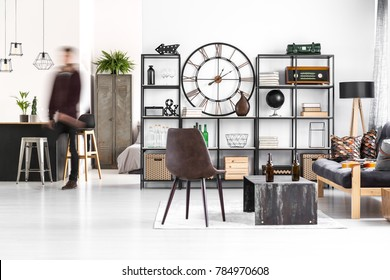 Brown chair and sofa next to a table with bottles in guy's room interior with kitchenette and clock on the wall