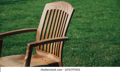 A brown chairs kept in a green sports ground