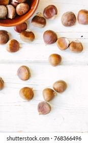 Brown chestnuts over wooden surface.