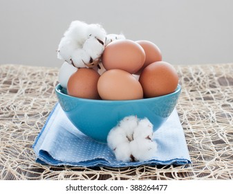 Brown chicken eggs in a blue bowl, and cotton flowers on a blue napkin