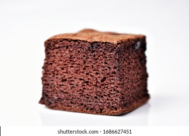 Brown chocolate cake, divided into small pieces on a white background
