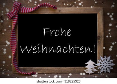 Brown Christmas Blackboard With German Text Frohe Weihnachten Means Merry Christmas Greeting Card. Christmas Decoration, Christmas Tree, Snowflakes, Red Loop. Wooden Background. Vintage Rustic Style.