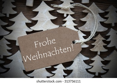 Brown Christmas Label With Ribbon On Wooden Christmas Trees Background. Vintage Style.Label With German Text Frohe Weichnachten Mean Merry Christmas For Christmas Or Season Greetings.Close Up Or Macro