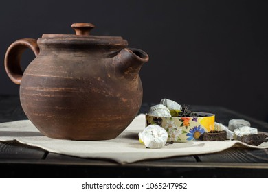 Brown clay teapot on wooden background and brewing green Chinese tea tabletsand post cards/ Vintage dishes/ Retro filter.