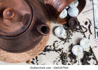 Brown clay teapot on wooden background and brewing green Chinese tea tabletsand post cards/ Vintage dishes/ Retro filter. Top view