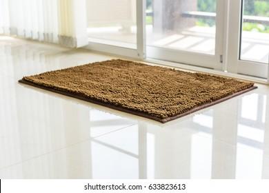 Brown cleaning door mat on the floor.