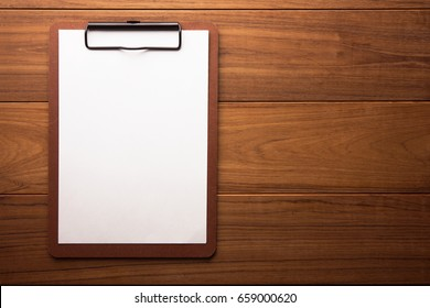 Brown clipboard with blank white paper on wooden surface, with plenty of copy space.